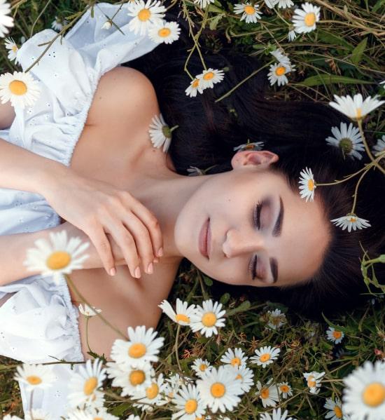 Девушка лежит на траве, вокруг ромашки