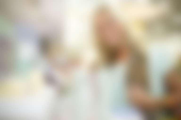 Блондинка выбирает крем в магазине