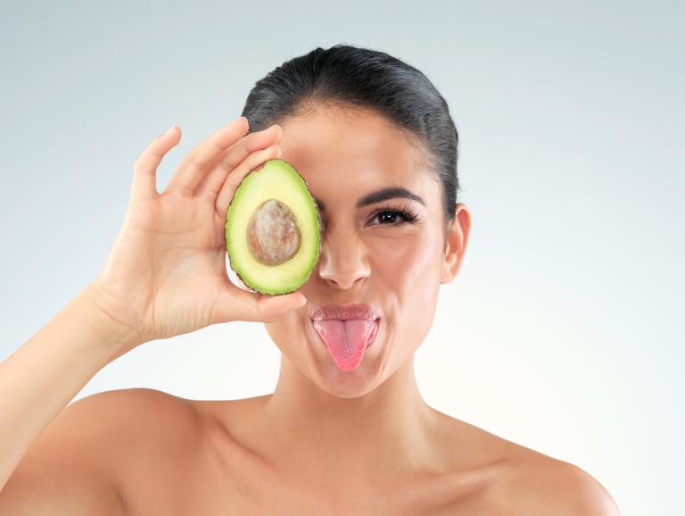 Женщина с высунутым языком держит у лица половинку авокадо