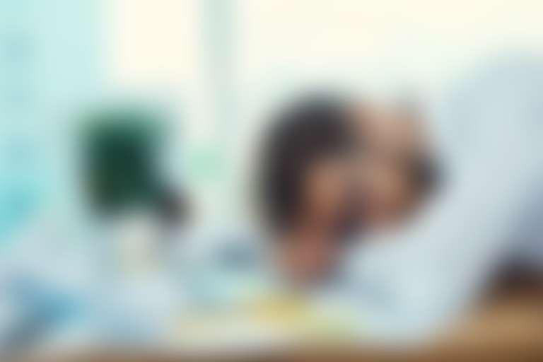 Молодой человек, спящий на рабочем столе