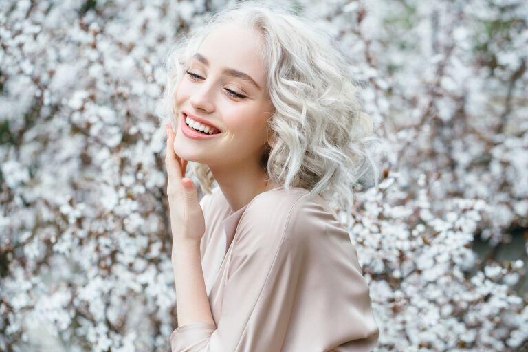 Улыбающаяся пепельная блондинка на фоне белых цветов