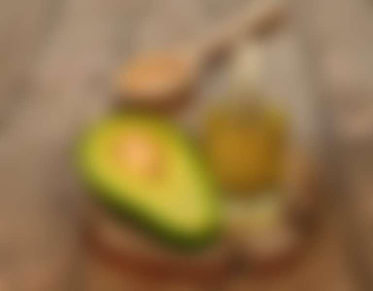 Половинка авдокадо и масло авокадо в бутылочке на деревянной поверхности