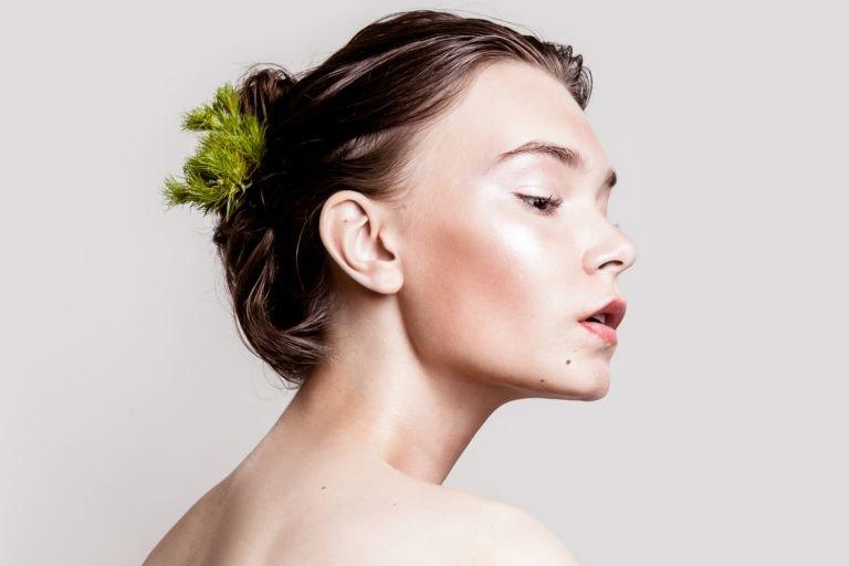 Полупрофиль обнаженной девушки с сияющим макияжем