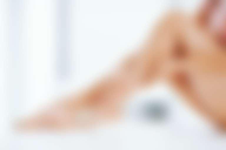 На обнаженные ноги девушка наносит крем