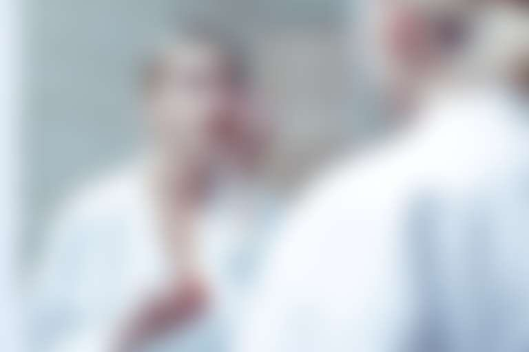 девушка стоит перед зеркалом и наносит средство для глаз