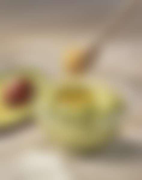 половинка авокадо, пюре из авокадо в стеклянной миске, мед на деревянной палочке