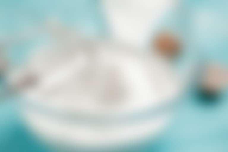 взбитый миксером белок в стеклянной миске на голубом столе, рядом яичная скорлупа
