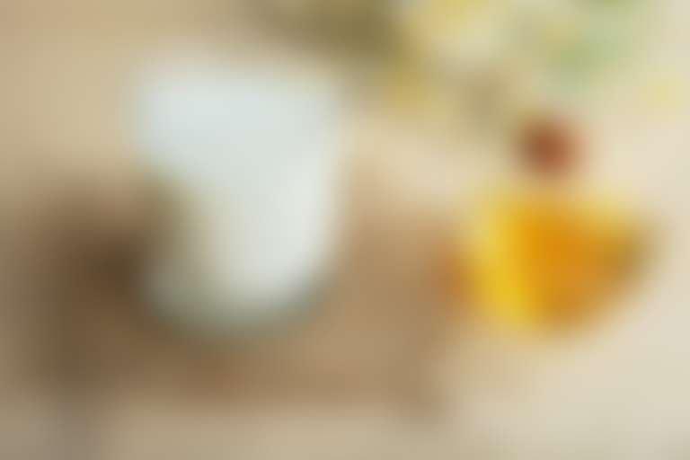 На столе стоит стакан со сливками и миска с медом для приготовления маски.