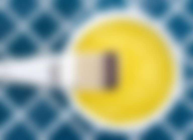 В белой миске жидкость желтого цвета — мед или яичный желток, рядом кисть для нанесения маски.