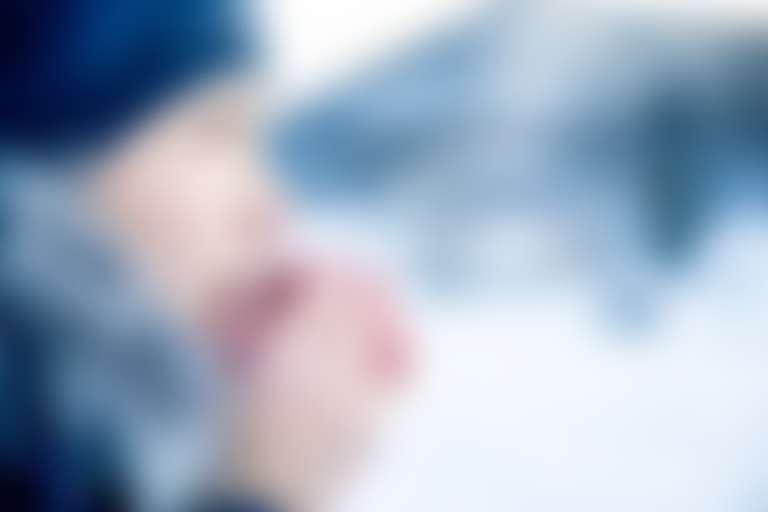 Девушка в  вязаной шапке согревает дыханием замерзшие руки на фоне зимнего пейзажа