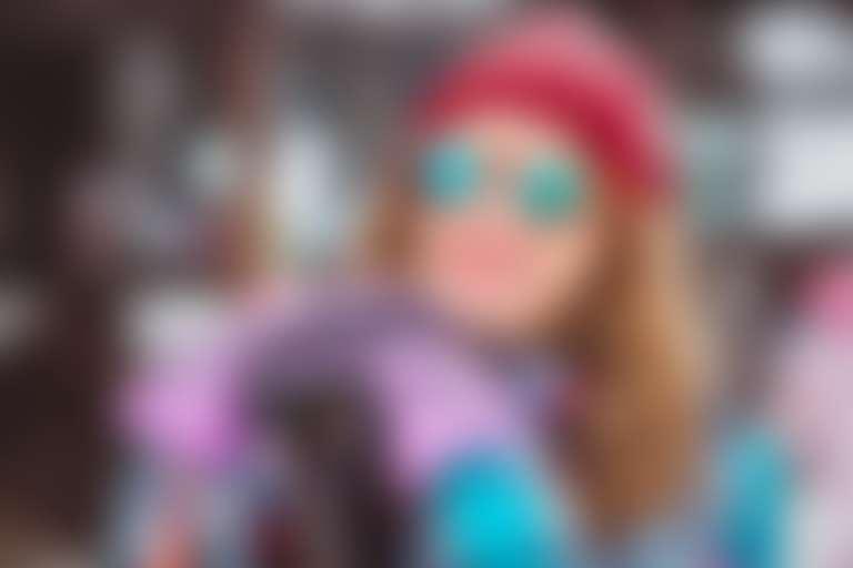 Улыбающаяся девушка в красной вязаной шапке, солнцезащитных очках и лыжных перчатках опирается на лыжи