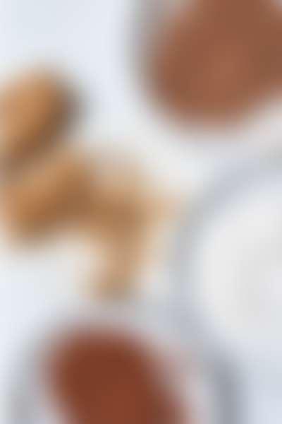 в белых тарелках насыпаны кокосовая стружка, какао-порошок для приготовления домашней косметики