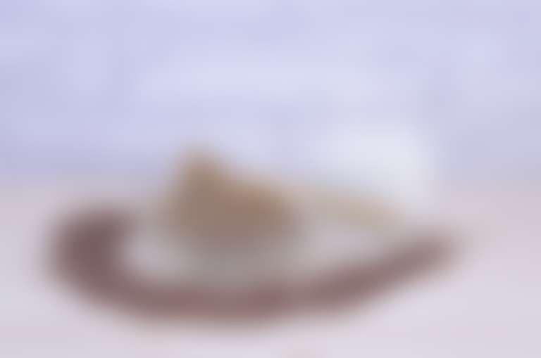 семена льна рассыпаны на столе полукругом вокруг розетки с молотым семенем льна и деревянной ложкой и стакана с молоком