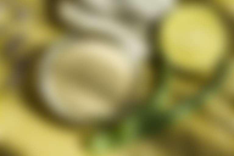 на светло-коричневом деревянном столе два побега алоэ, половинка лайма, цветы лаванды, серо-бежевый порошок глины в стеклянной плошке, друг на друге два серых камня для спа