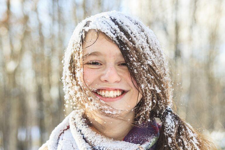 Улыбающаяся девушка без шапки, засыпанная снегом
