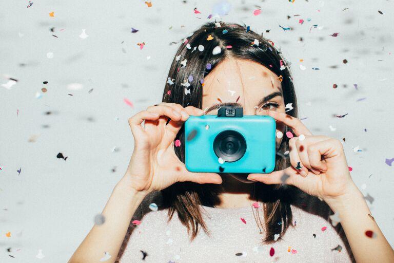 кареглазая брюнетка с ухоженной кожей на фоне праздничного разноцветного конфетти держит голубой фотоаппарат
