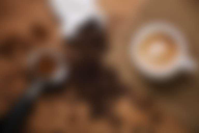на деревянной поверхности кофе в зернах высыпан из белого пакета, молотый кофе в ложке для кофе-машины и белая чашка со сваренным кофе на холщовой салфетке