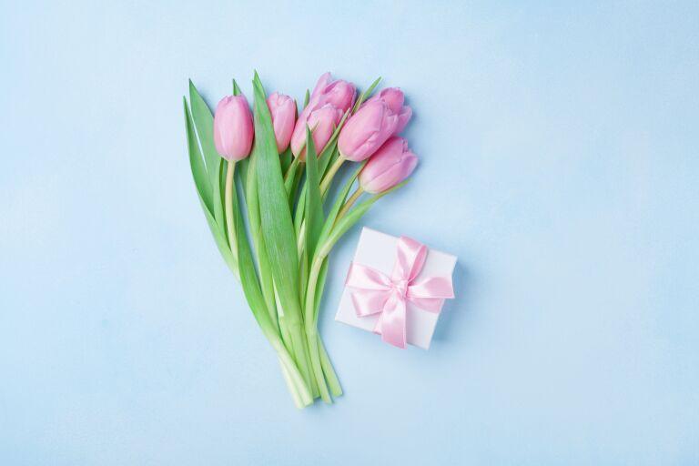 на столе букет тюльпанов и коробочка с подарком на 8 марта
