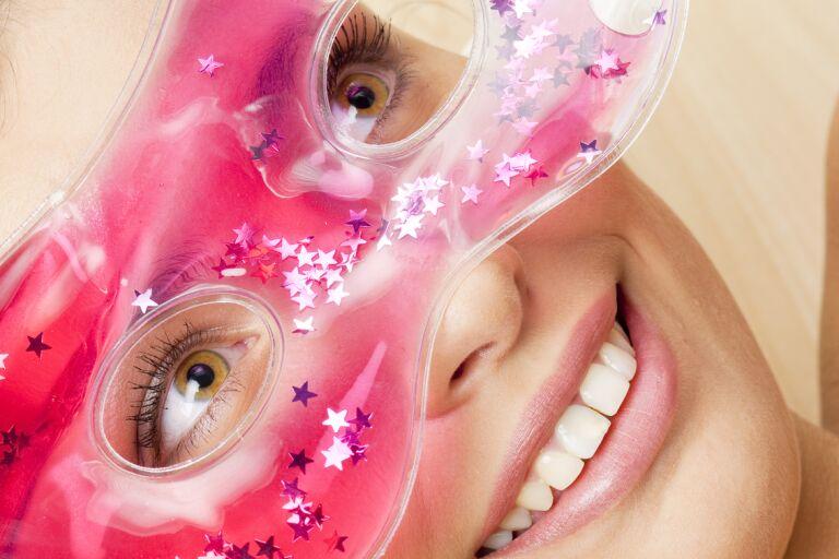 девушка с ухоженной кожей улыбается и держит на уровне светло-карих глаз розово-красную гелевую маску с блестками