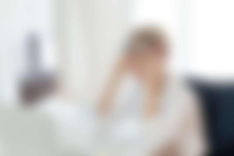Усталая девушка в белой блузке в офисной обстановке приподнимает очки и трет глаза