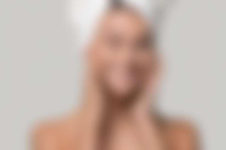 Девушка с полотенцем на голове делает упражнения для омоложения лица
