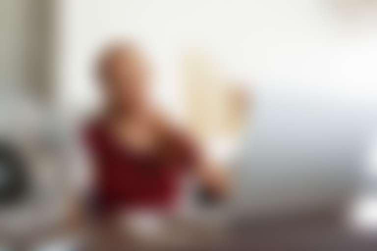 усталая девушка в красной майке сидит за компьютером, стресс приводит к проблемам кожи