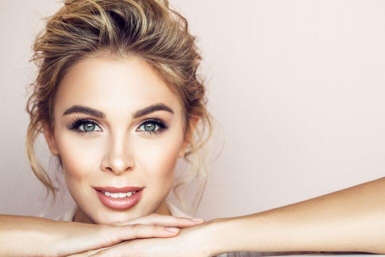 женское лицо с идеальной кожей и идеальным макияжем опирается подбородком о руки