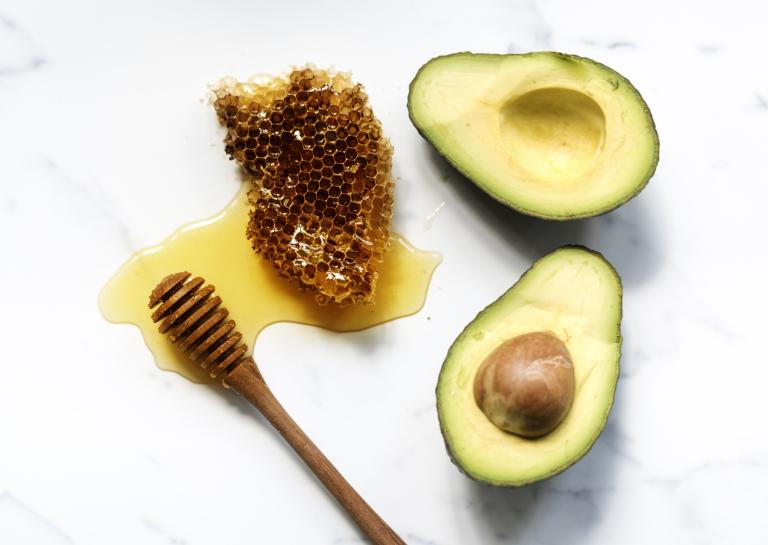 половинки авокадо и мед с сотами для приготовления домашней омолаживающей маски