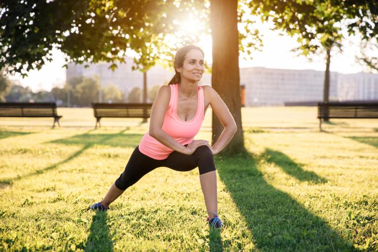 женщина в парке делает зарядку, занимается фитнесом