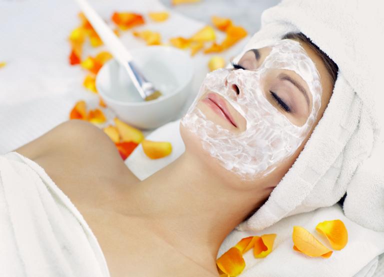 девушка с косметической маской на лице лежит среди оранжевых лепестков