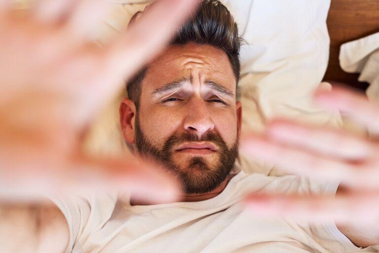 мужчина закрывается руками от фотокамеры, потому что у него отекает лицо