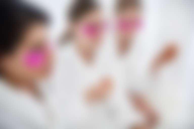 три девушки в банных белых халатах с патчами на глазах и бокалами в руках