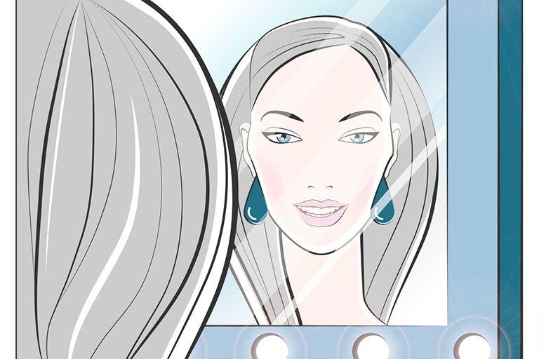 девушка смотрит в зеркало с подсветкой чтобы сделать безупречный макияж