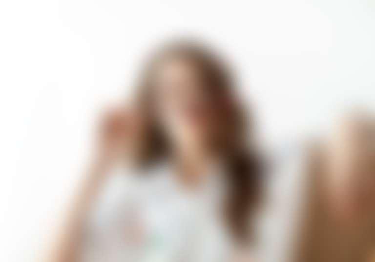 девушка в перепачканной красками белой блузе и с красным маникюром сидит перед холстом и держит кисточку как усы Дали
