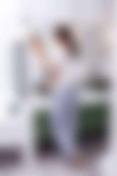 Девушка в пижаме в ванной перед зеркалом протирает лицо ватным диском