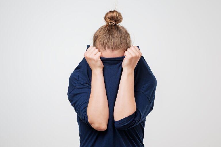 Девушка спрятала лицо в свитер, чтобы скрыть забитые поры на лице