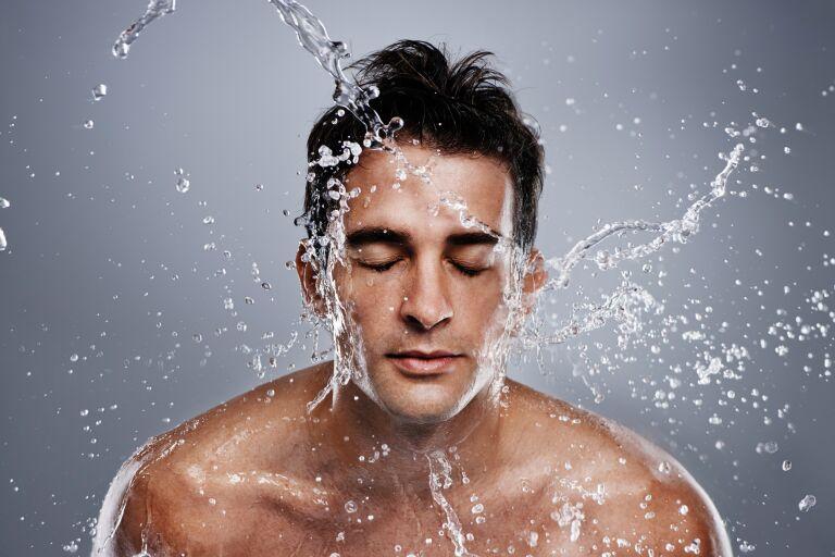 Мужчина стоит под душем