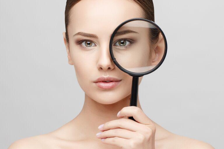 девушка с идеальной кожей смотрит в увеличительное стекло