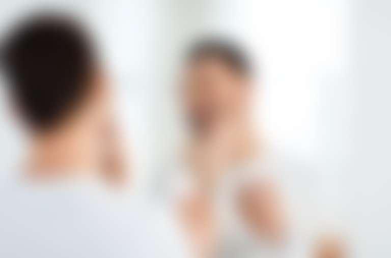 мужчина с короткой бородкой наносит перед зеркалом крем на лицо