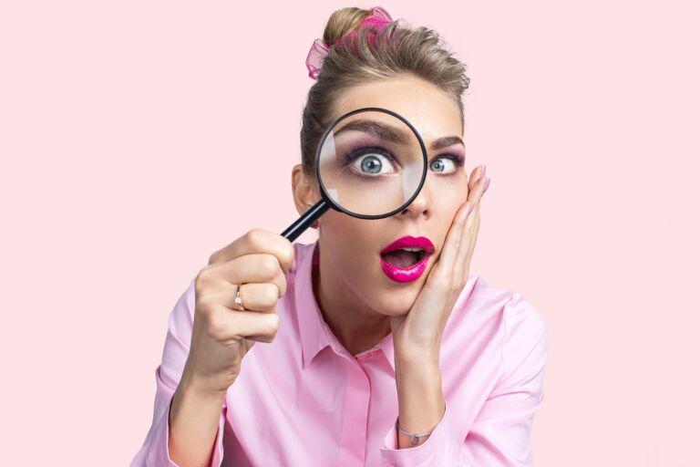 девушка смотрит в лупу и хорошо видно, какая у нее гладкая кожа вокруг глаз