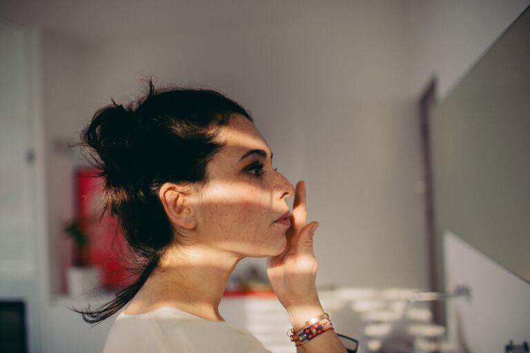Женщина перед зеркалом делает точечный массаж лица