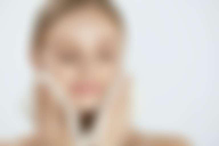 Девушка приложила к нижней челюсти горячее полотенце для очищения кожи