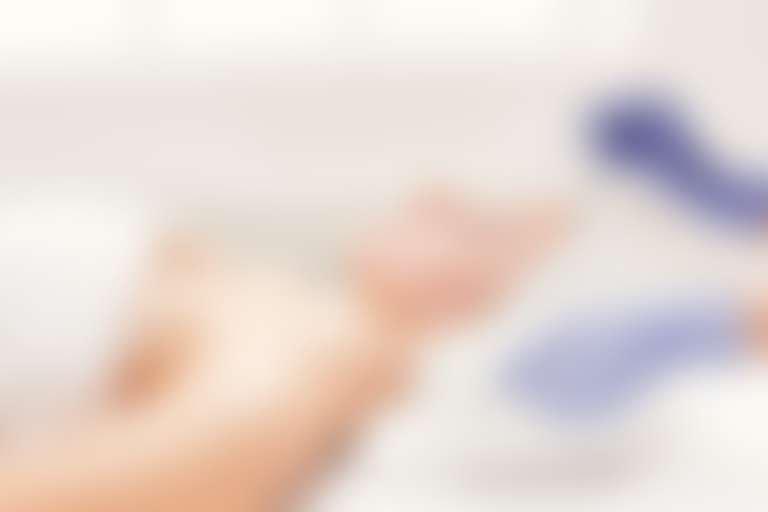 косметолог в перчатках проводит процудуру миндального пилинга лица