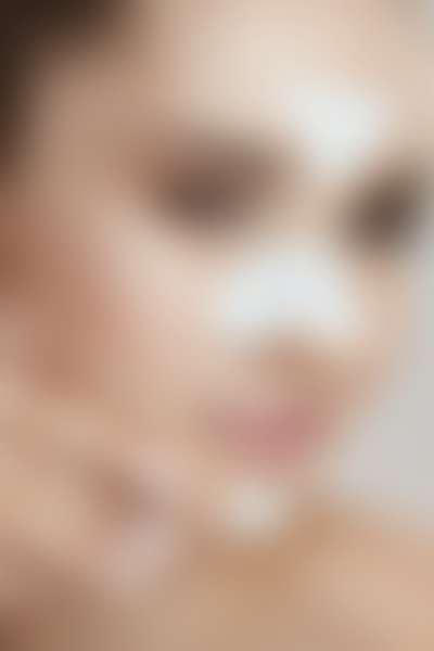 лицо кареглазой девушки с белыми патчами в Т-зоне для очищения пор