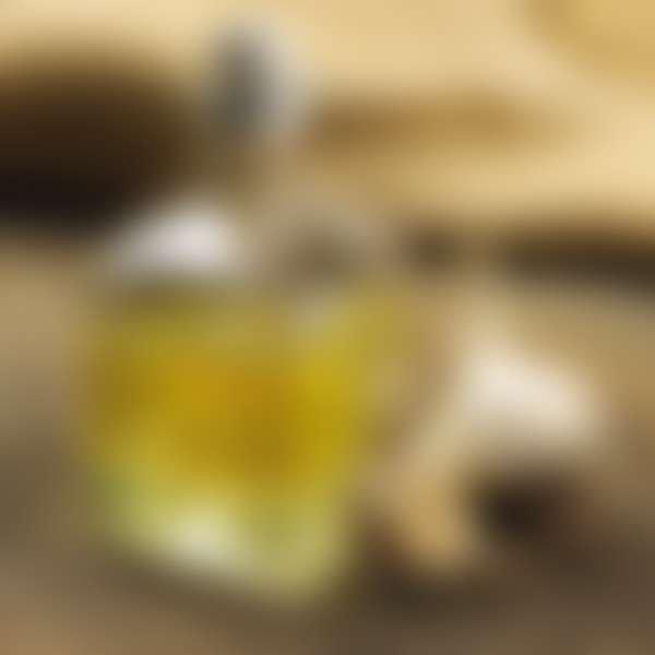 бутылочка с растительным маслом и головка чеснока для приготовления косметической маски