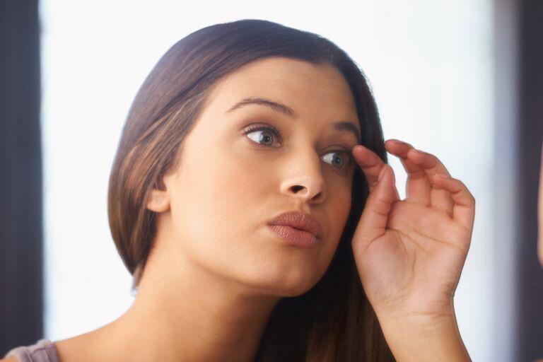 темноволосая красивая девушка с ухоженной кожей смотрит в зеркало и трогает веко и ресницы