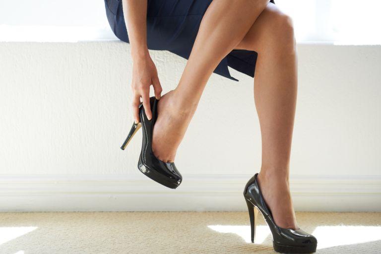 женская рука надевает снимает туфлю на высоком каблуке с усталых ног