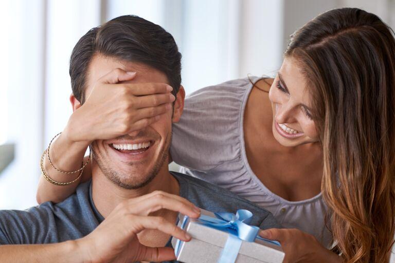 девушка закрывает рукой глаза молодому человеку и дает ему в подарок набор косметики
