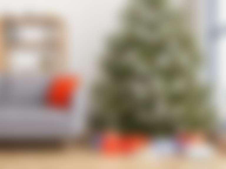 в светлой комнате наряженная в белые игрушки новогодняя елка и разноцветные коробки с подарками под ней косметика в подарок