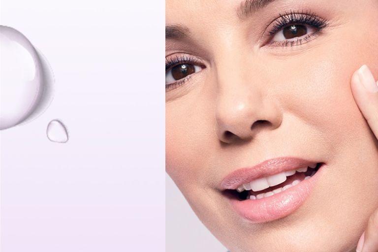 женщина с ухоженной кожей приложила пальцы к щеке, слева капли воды для увлажнения кожи